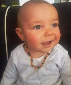 Baby wearing amber multi-coloured teething necklace